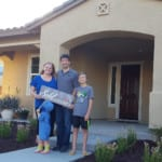 family with sold by Yvette Larson sign in front of Mountain House home