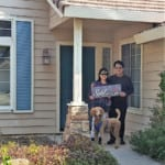 Haward, his wife, and dog in front of their new home