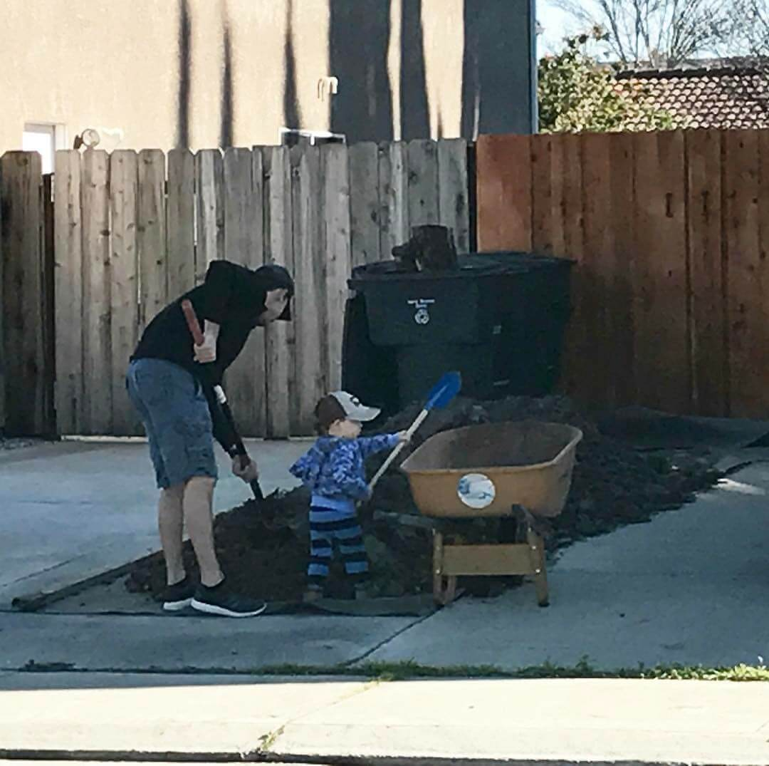 Sergey with his son, shoveling during a project in Tracy