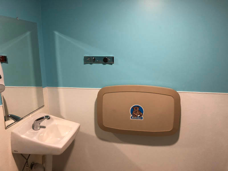 sink and diaper changing station with blue and white wall
